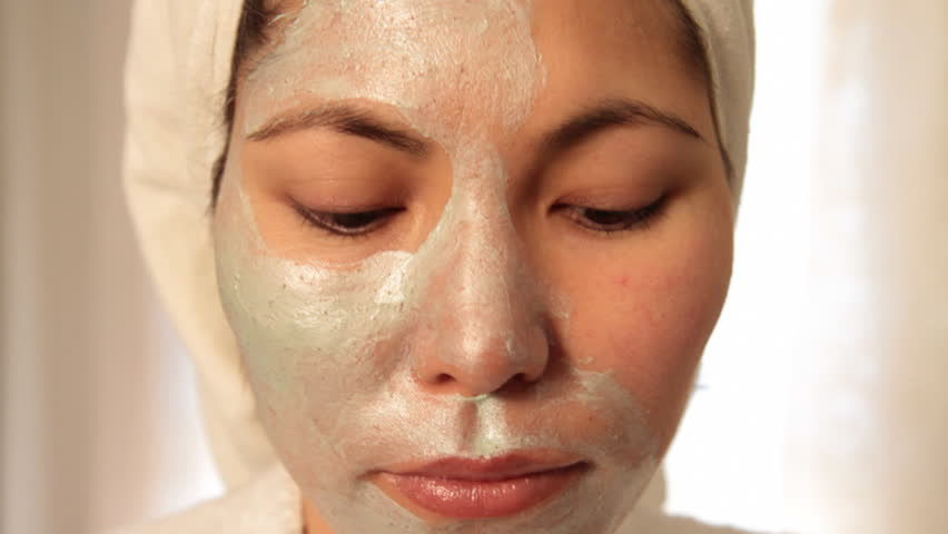 Young Asian woman looks into camera and applies scrub on her face