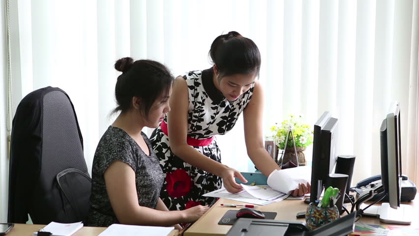 Two attractive Asian female young adult office workers collaborate together as they work in the office in Bangkok, Thailand.   Shutterstock HD Video #7204411