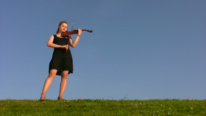 young woman stands on hill against blue sky and plays violin