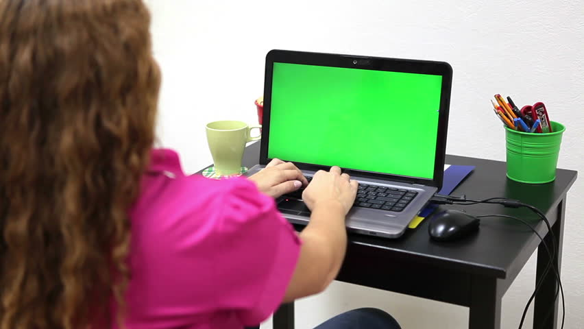 Successful woman shaking clenched fists when working at green screen laptop in office #7261201