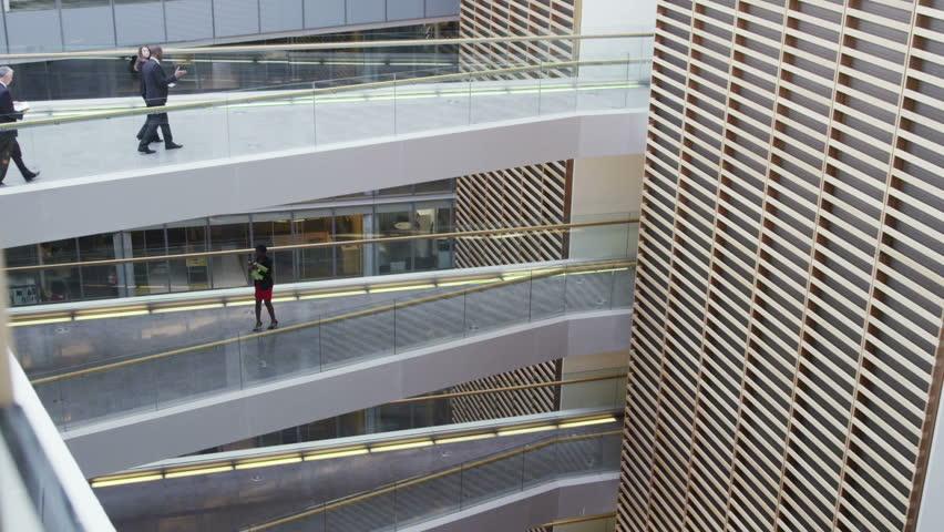 Business team meet & shake hands between floors of large modern office building | Shutterstock HD Video #7265251