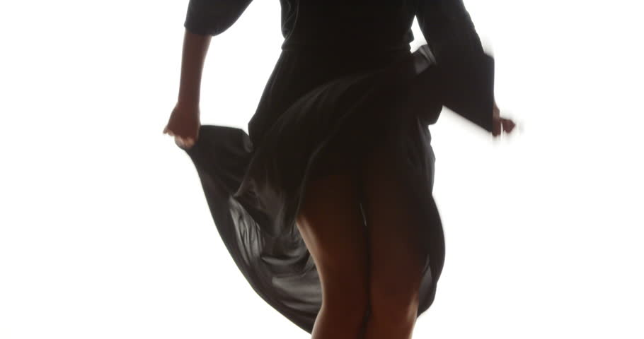 Hips and legs of black woman dancing in long flowing dress