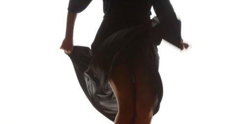 Hips and legs of black woman dancing in long flowing dress
