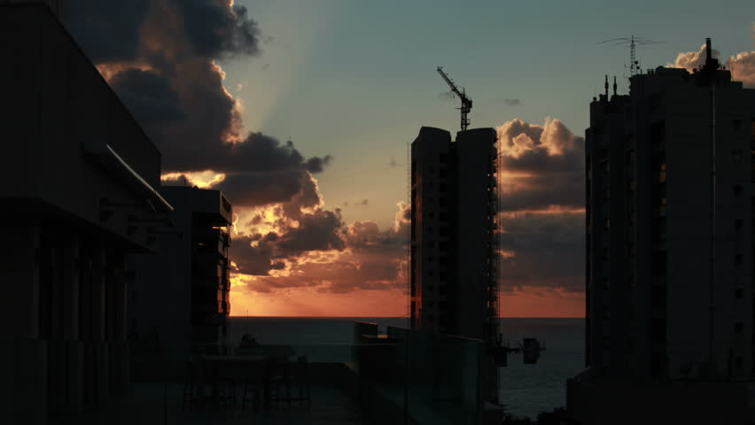 Time lapse of Sunset over city of Beirut, Lebanon. Thick cumulus clouds are lit by the setting Sun which appears behind the building just as it starts disappearing into the sea.