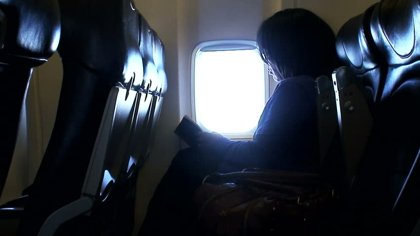 Woman reading a book whilst on a airplane flight 2