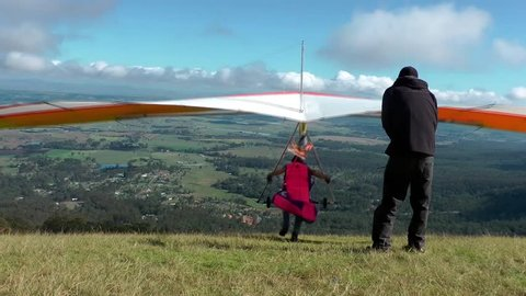 Hang gliders take off from mountain top