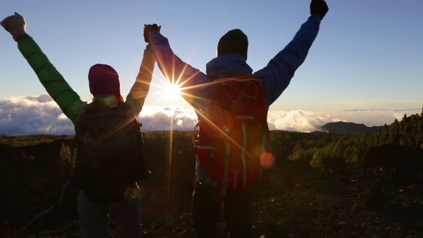 Success, achievement and accomplishment concept with hiking people cheering jumping, running and celebrating of joy on trekking hike outside. Hikers having fun at sunset.