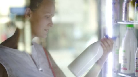 Woman opening fridge and choosing milk at the shop. View through the glass fridge door