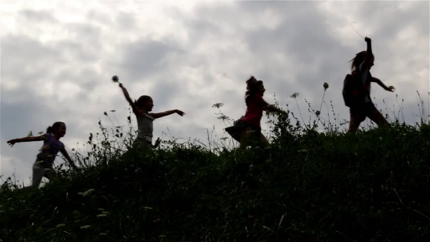 Silhouette of children. Group of children playing on the field. Young girls and boy running on right over the hill. Young boy leads a group of little girls. Childhood. Kids. Teens. Cloudy sky. 25 fps.   Shutterstock HD Video #7377889