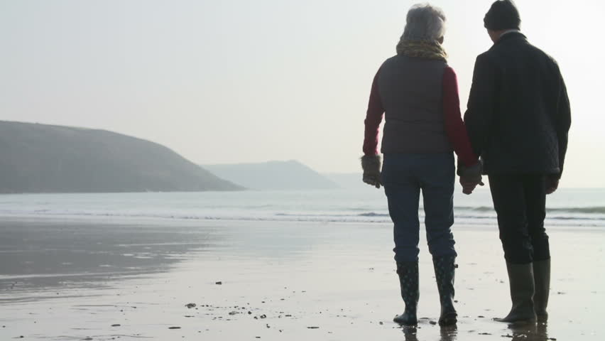 Rear View Of Senior Couple Walking On Beach In Slow Motion