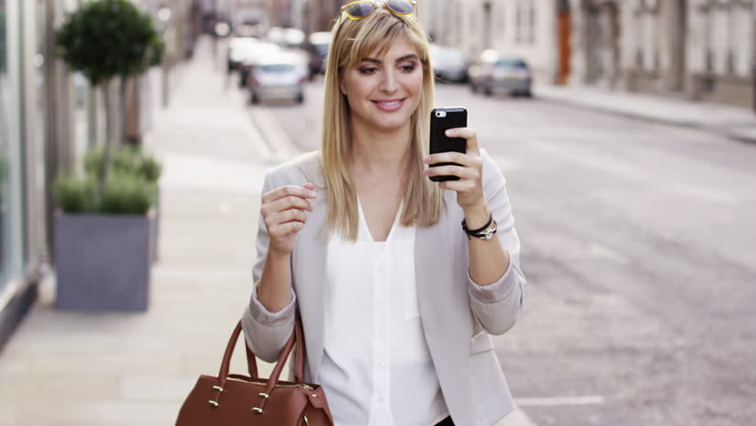 Attractive blonde business woman using smartphone commuter in city london - RED EPIC DRAGON 6K