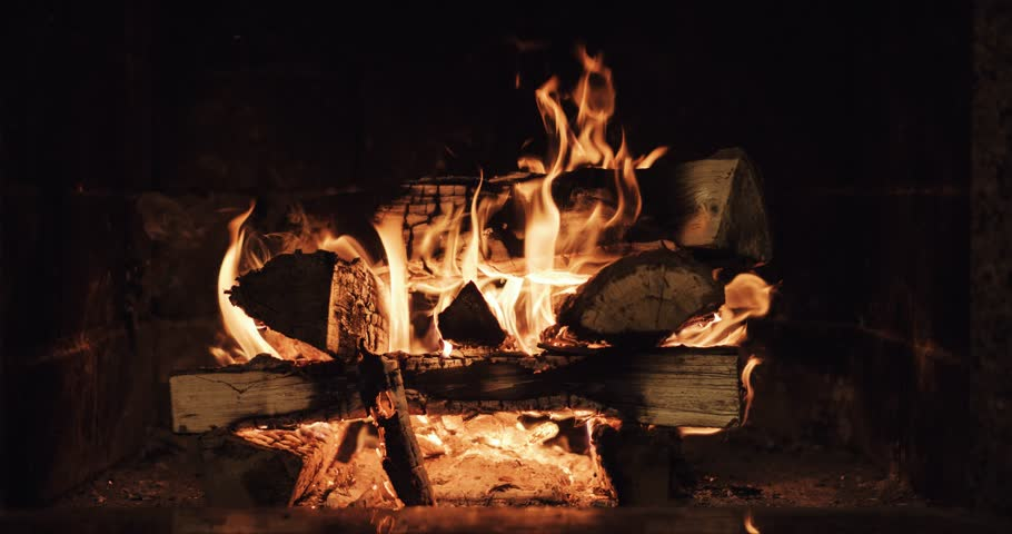Slow motion of Fireplace burning. Warm cozy burning fire in a brick fireplace close up. Cozy background. Filmed at  120 fps 4k graded from RAW