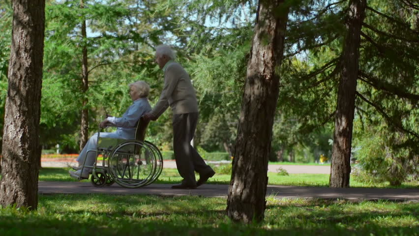Man pulling his wife in wheelchair in the woods passing by camera