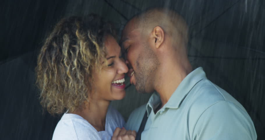 Black couple kissing under umbrella