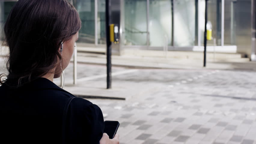Attractive business woman commuter using smartphone walking in city of london - RED EPIC DRAGON 6K | Shutterstock HD Video #7402276