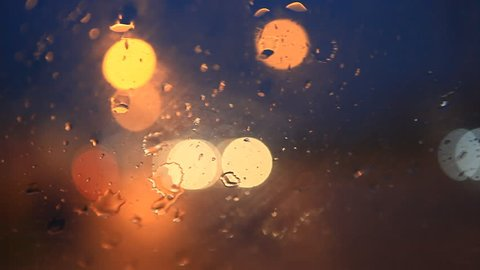 rain flows and wipers on the front windshield glass window of car stopping beside the road with beautiful colorful blurry light of traffic outside on the road, broken heart, sad, cry scene