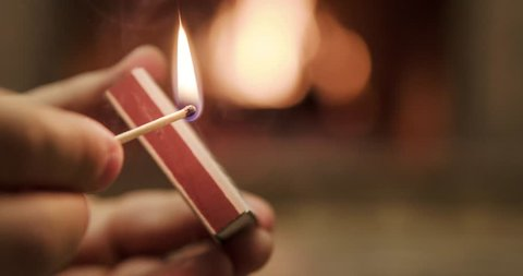 Striking and lighting wooden match in slow motion in front of a fireplace burning. Slow motion 120 fps. 4k graded from RAW.