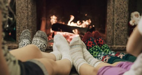 Feet in woolen socks warming by cozy fire in Christmas time in slow motion. Family with two kids warming their feet by the fireplace in winter time. Filmed at 120 fps 4k graded from RAW