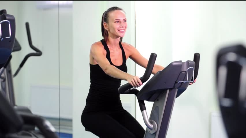 Happy Yang Woman Doing Indoor Biking In A Fitness Club Stock