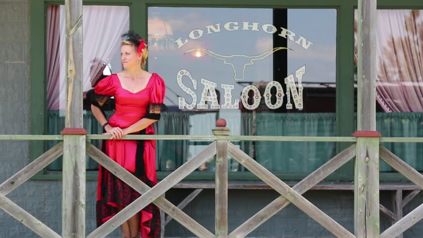 Deadwood, South Dakota, July 2014: A woman tourist in western era clothing stands in front of the Longhorn Saloon near Deadwood, South Dakota, July 2014.