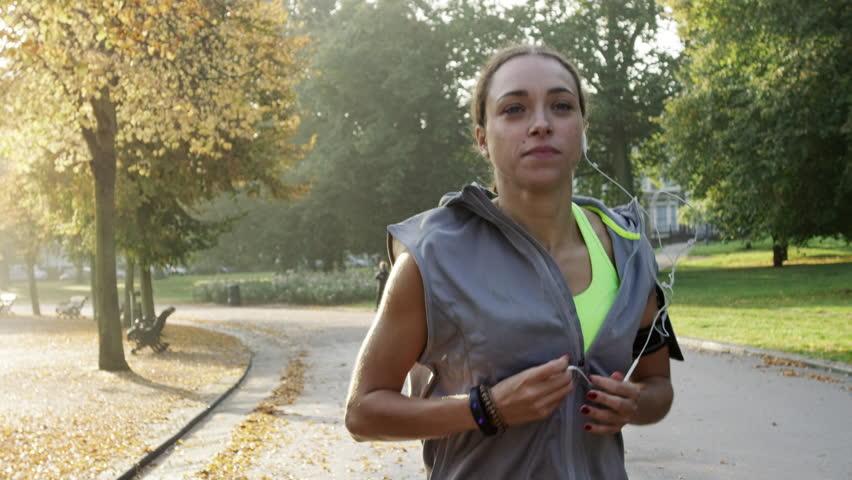 Runner woman running in park exercising outdoors fitness tracker wearable technology #7455721