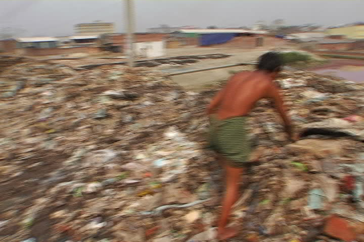 A young man digs through a mountain of trash near the shores of a toxic pond, in a Bangladesh slum.