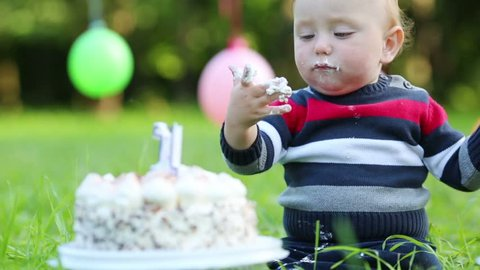 Cute stained happy baby eats cake with candle in form of 1 at summer park