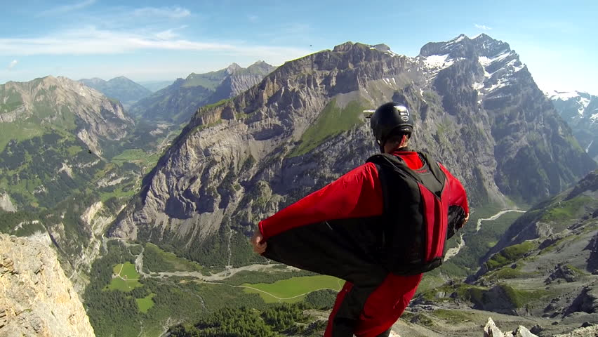 A base jumper in a wingsuit leaping off a from a rocky cliff, gliding down over a green landscape