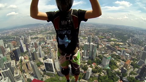 Two base jumpers jump together from a skyscraper, opens their parachutes in mid air before maneuvering it over the cityscape