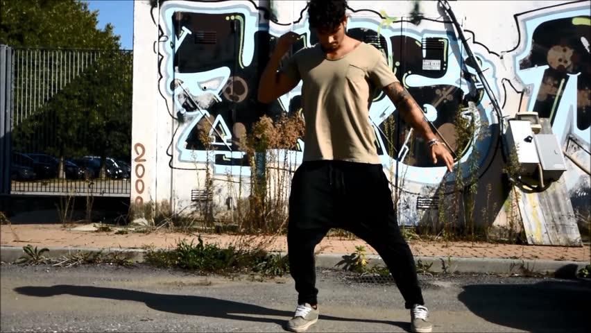 Trendy cool young man doing break dance in the street