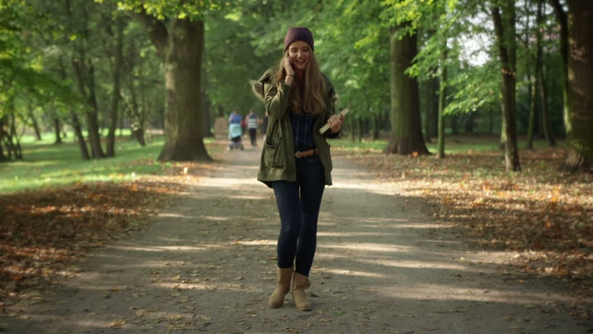 Attractive young woman with a book talking on mobile phone while walking in beautiful autumn park. Happy woman talking on mobile phone, outdoors   Shutterstock HD Video #7505797