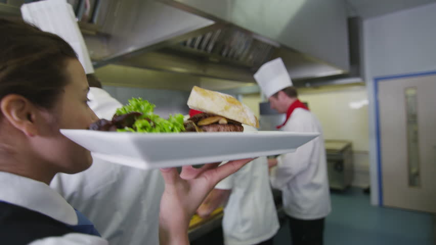 Restaurant Kitchen Video waitress collects her order from the chef in a busy hotel or