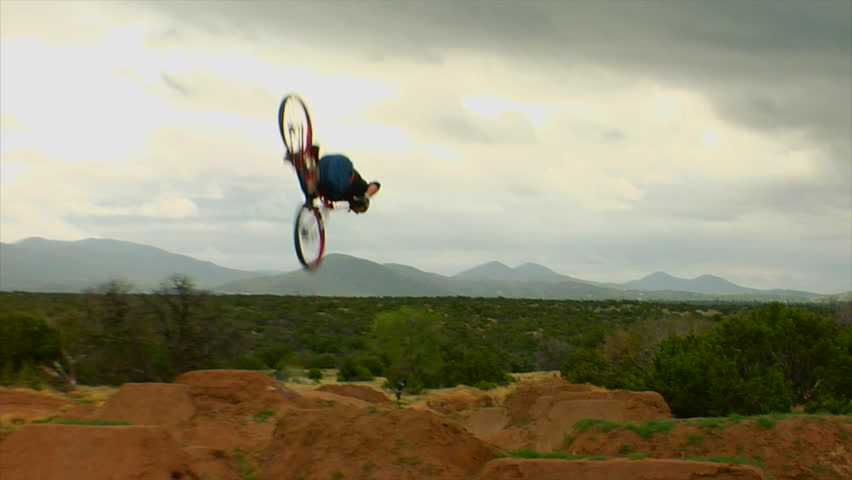 A mountain biker performs dirt jumps and tricks in a park #7533811