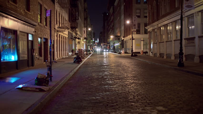 NEW YORK - AUG 1, 2014: desolate dark SoHo cobblestone street at night with Chrysler Building in background. SoHo is a neighborhood south of Houston Street in Manhattan, NYC.