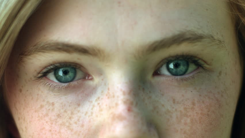 A CloseUp Of A Young Woman's Eyes, She Stares Into Camera, Then Her Eyes Brighten As She Smiles #7610401