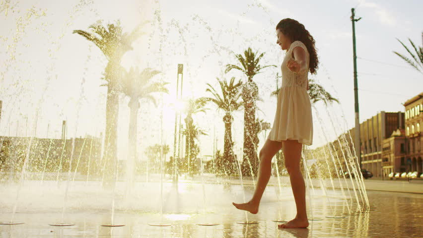 Beautiful woman cooling off in fountain in the city in summertime | Shutterstock HD Video #7618681
