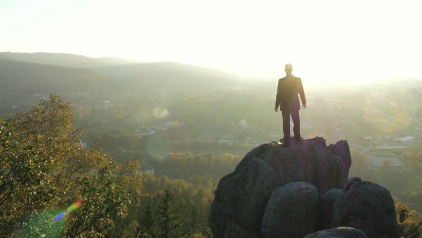 Office worker standing on a lonely rock | Shutterstock HD Video #7638490