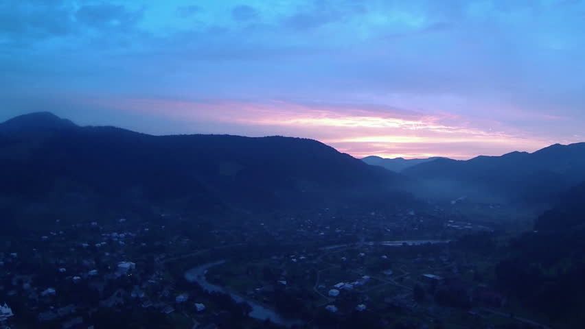 Red sunset over  village in mountain valley. Aerial shot panorama | Shutterstock HD Video #7641721