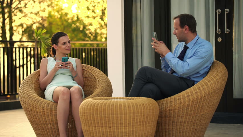 Businessman taking photo of beautiful businesswoman on terrace