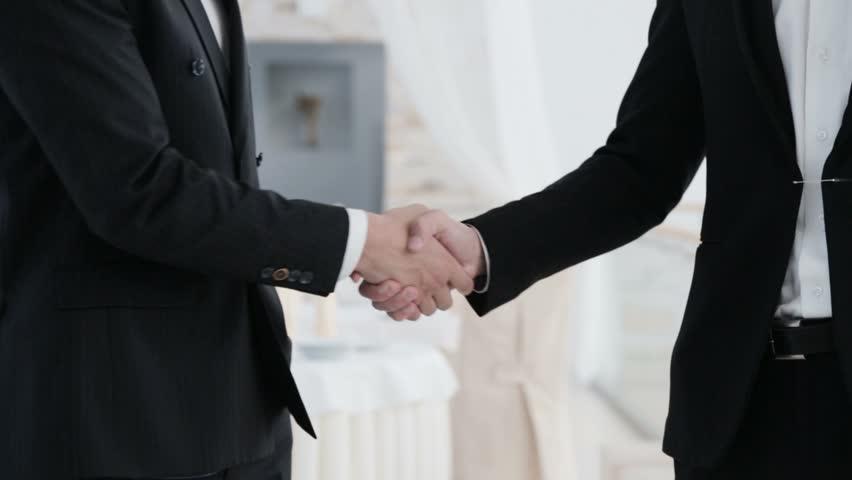 Handshake with both hands. Normal handshaking and handshaking with both hands. Two businessmen doing handshake with both hands. | Shutterstock HD Video #7700761