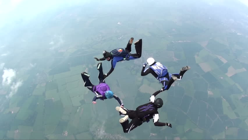 Four skydivers in freefall doing formations