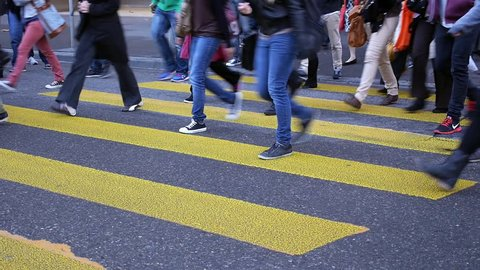 Legs of people crossing zebra crosswalk.  People crossing a street in Zurich, Switzerland during the morning rush hour.