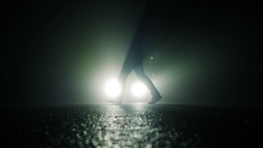 Mystical Silhouette Of Man Walking Towards Camera In Dark