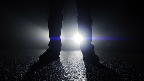 backlight silhouette of mystery man standing in front of car light beams