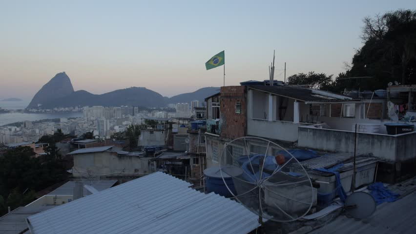 Aerial favela flight over Brazil flag waving in wind with Sugarloaf Mountain in the background