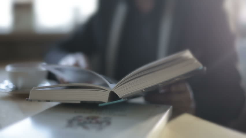 A man in a cafe drinking coffee and reading a book. Slow motion