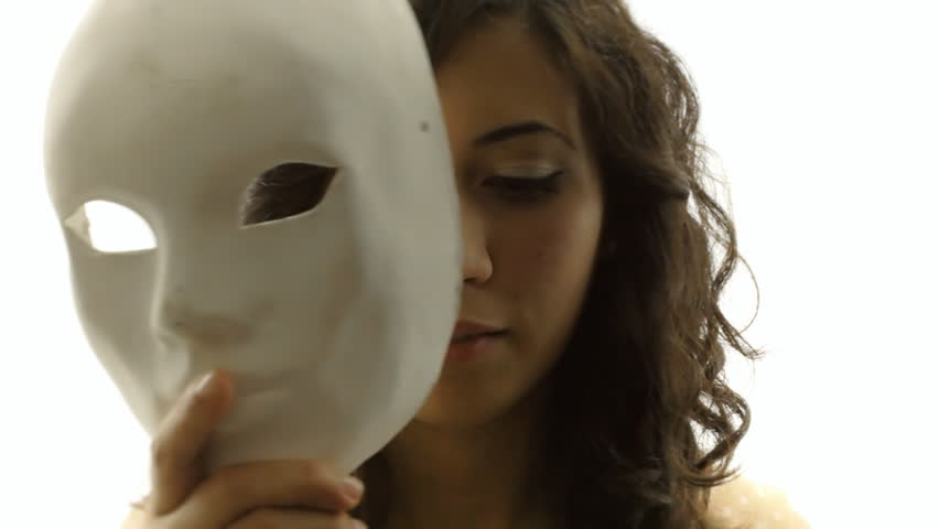 The silhouette of a mysterious young woman hides her face behind a plain white mask. Close-up shot.