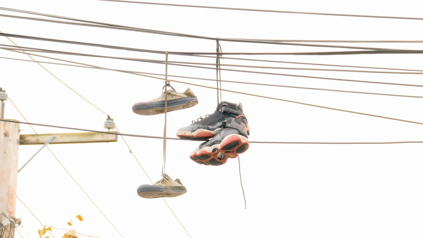 Sneakers hanging from telephone wire in the city is a symbol for a drug dealer or gang turf