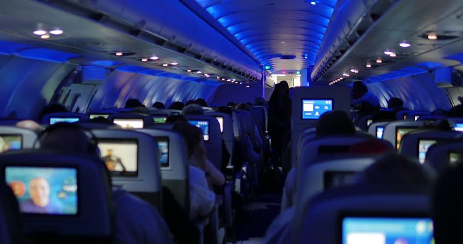People watching in-flight entertainment inside passenger aircraft during flight. 4K UHD.