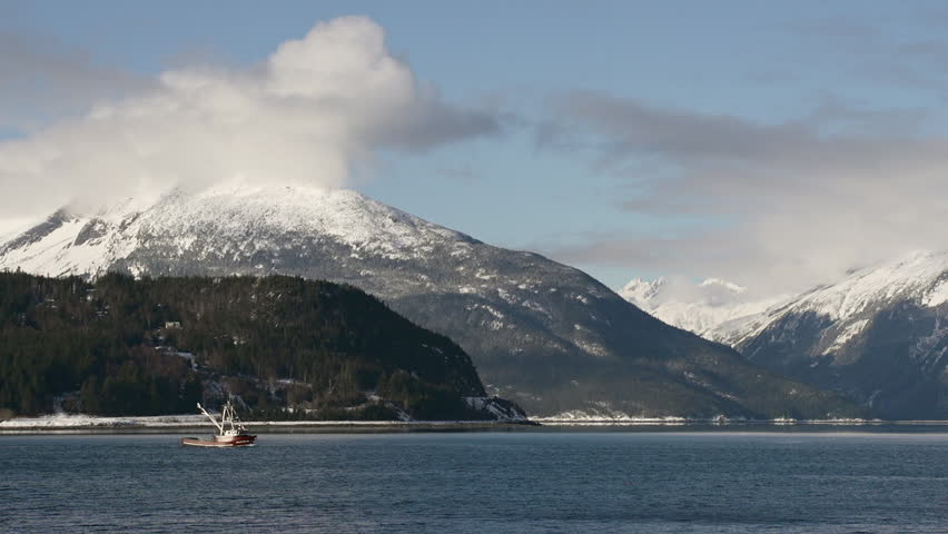 Fishing vessel, likely out for cod or crab, heading south from Haines Alaska in the Lynn Canal during winter.